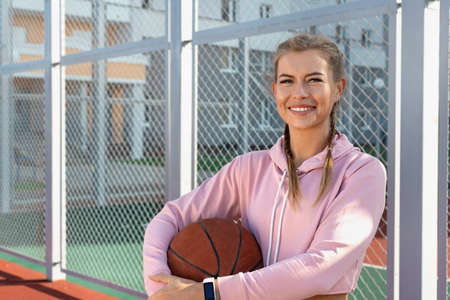 Confident smiling sporty woman wearing pink hoodie holding basketball on outdoor court. Healthy lifestyle concept.