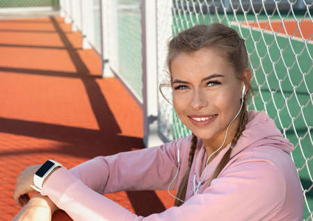Portrait of confident smiling sporty woman wearing pink hoodie with white fitness bracelet and headphones on outdoor court. Healthy lifestyle concept. 免版税图像