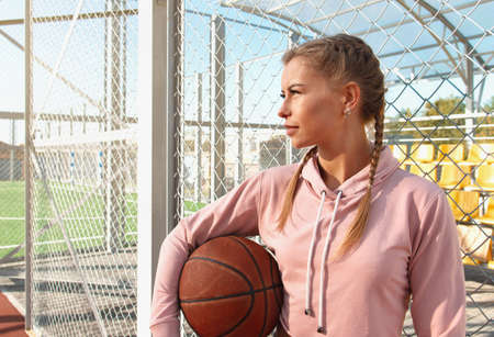 Confident young sporty woman wearing pink hoodie holding basketball on outdoor court. Healthy lifestyle concept.