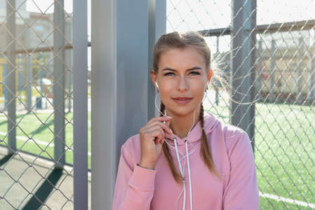 Portrait of confident sporty woman wearing pink hoodie with white headphones on outdoor court. Healthy lifestyle concept. 免版税图像