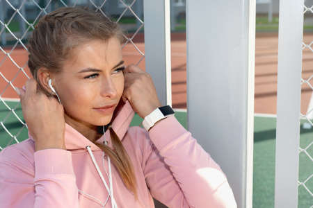 Portrait of confident young sporty woman wearing pink hoodie with white fitness bracelet and headphones on outdoor court. Healthy lifestyle concept.