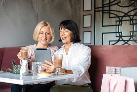 Two mature women chatting and using the tablet device while having lunch in cafe. Leisure concept of mature people Stock Photo