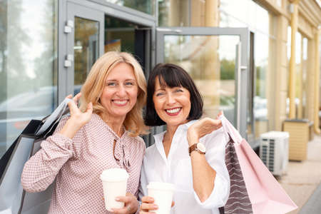 Two mature women having fun while doing shopping and drinking coffee. Pastime concept of mature people Stock Photo