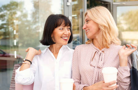 Two mature women having fun while doing shopping and drinking coffee. Pastime concept of mature people