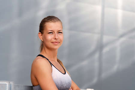 Portrait of healthy fitness sporty smiling woman early in the morning city at sunrise.Healthy lifestyle concept. Stock Photo