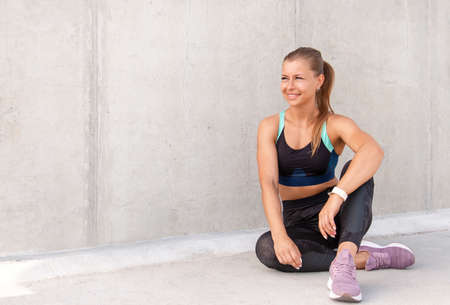 Fitness sporty woman is sitting and having a break after running early in the morning city at sunrise. Healthy lifestyle concept. Stock Photo