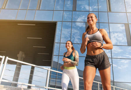 Two women exercising by jogging in the city while sun is setting. Healthy lifestyle concept.