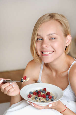 Beautiful young blonde woman eating her oatmeal with berries for breakfast in the morning. Healthy lifestyle concept Stock Photo