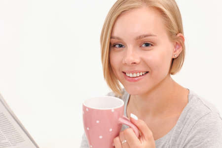 Beautiful smiling young blonde woman drinking coffee and reading newspaper in the morning. Healthy lifestyle concept