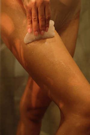 Close up shoot of woman's leg while doing anti-cellulite massage with scraper guache in shower. Beauty spa concept. Foto de archivo
