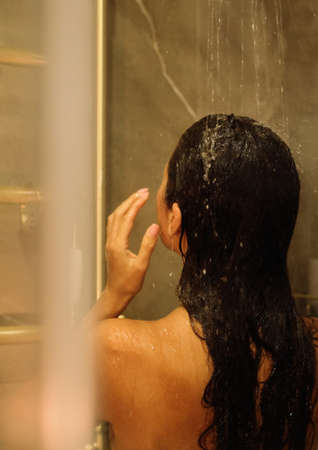 Back view of beautiful naked young woman taking shower in bathroom. Beauty spa concept. Foto de archivo