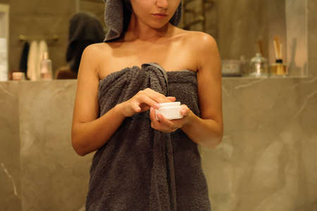 Young woman in a towel holds a jar with a cosmetic cream in her hands. Skin care products. Beauty spa concept.