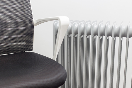 armchair stands near the oil heater on white background