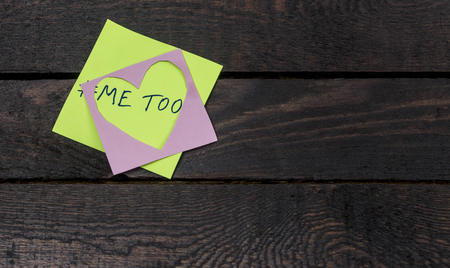 Metoo message written on pink heart paper on wooden background.