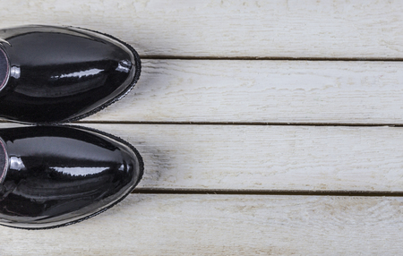 Black pair rubber galoshes stand on wooden background.