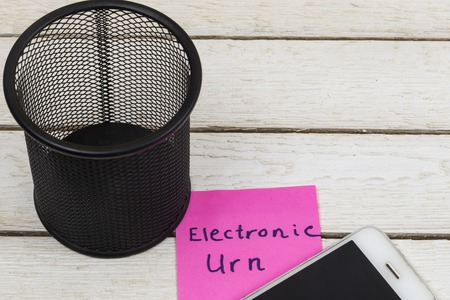 cell phone near trash can with the words: Electronic Urn. Stock Photo