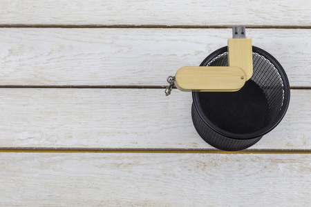 wooden flash drive in trash can on white background. Stock Photo