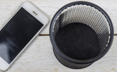 white cell phone near trash can, Electronic waste concept. Stock Photo