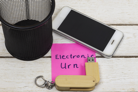 cell phone and flash drive near trash can with the words: Electronic Urn.