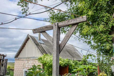 Village. Rural. Wooden pole for clotheslines in the yard of a small house overgrown with bindweed.
