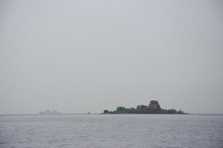 fort on the island, ship silhouette, sea and fog Stock Photo