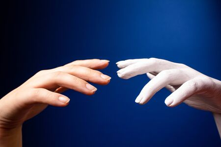 Hand gesture. Human gesture. Two hands are drawn to each other on a blue background. Hands on a background of blue wall