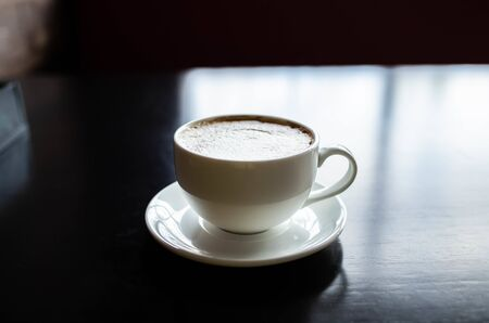 white cup with coffee on a black wooden table. The light reflected from the window is reflected on the table