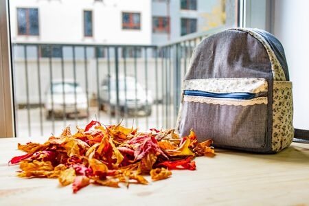 A backpack lying on a wooden table, next to many autumn leaves Фото со стока