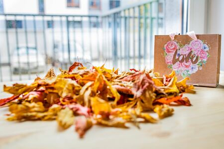 Autumn love concept. Dry autumn leaves on a table with a paper bag