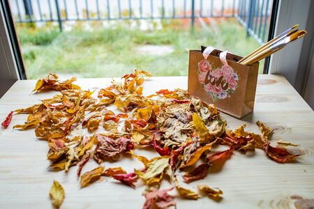 Art concept of autumn composition. Paper bag with autumn yellow dried leaves on a wooden table