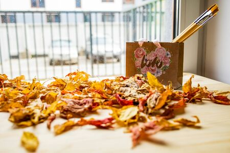 Art concept of autumn composition. Paper bag with brushes next to dried leaves on a wooden table Фото со стока