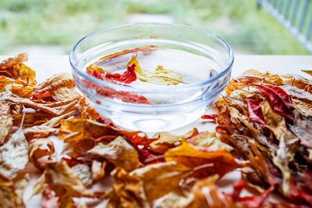 Bright autumn leaves float in water in a glass transparent bowl standing on a wooden table