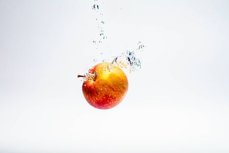 red ripe apple thrown into the water