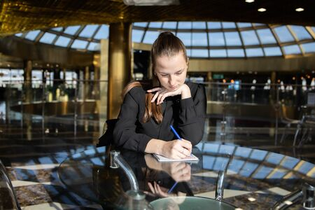 Business girl in black sits thoughtfully at a table and fills a document