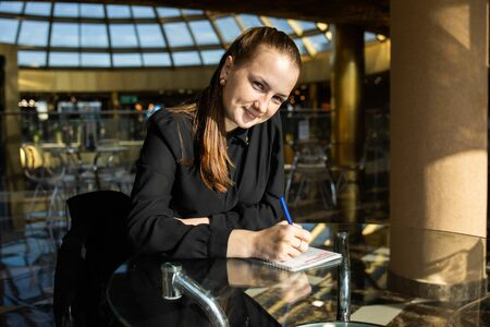 Business girl in black sits at a table, looks at the camera with a smile and fills out a document