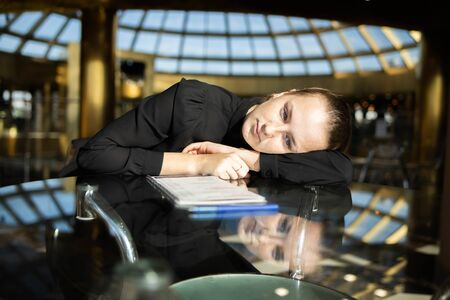 Business girl in black lay on the table, looking thoughtfully into the void Фото со стока