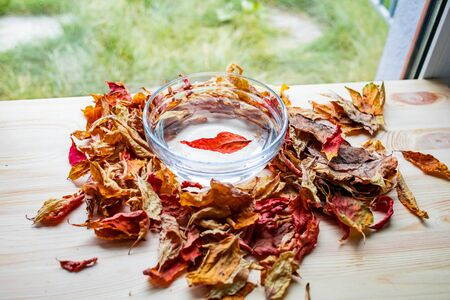 Bright autumn leaves float in water in a glass transparent bowl among many dry leaves Фото со стока