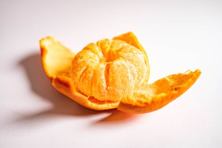 Bright juicy mandarin in the form of a flower isolated on a white background. Mandarin peel in the form of petals Фото со стока