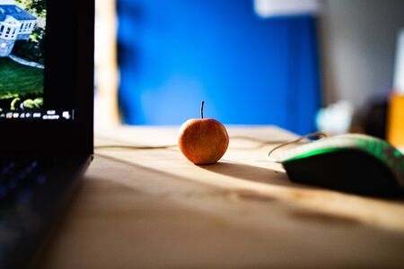 Small red apple on a wooden table with a laptop and a computer mouse Фото со стока - 131363174