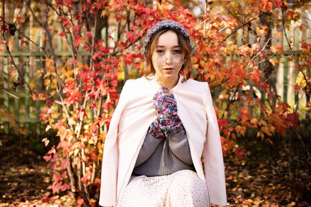 Beautiful elegant girl standing in a park in autumn against a background of red leaves. Warmly dressed woman in autumn
