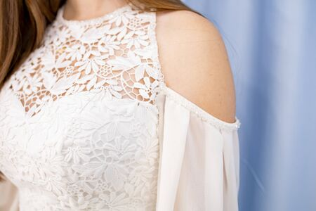 part of a white dress with lace on a woman. Beautiful white dress on the girls shoulder Фото со стока