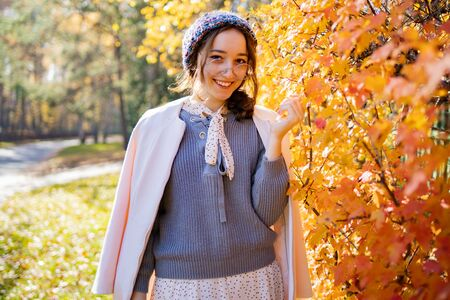 The girl in glasses stands on a background of red autumn leaves. Beautiful girl wrapped herself in warm clothes in autumn