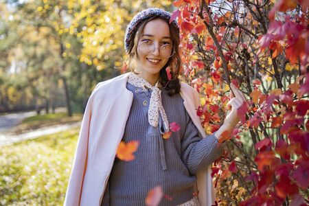 The girl in glasses stands on a background of red autumn leaves in the fall. Autumn leaves fall on a girl