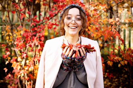 Beautiful slender girl with glasses standing on a background of red autumn leaves. Warmly dressed woman in autumn smiling