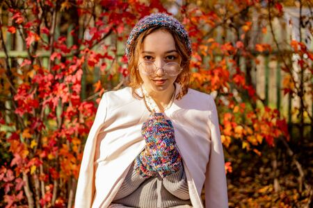 Beautiful slender girl standing on a background of red autumn leaves. Warmly dressed woman in autumn