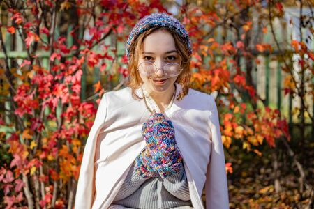 Beautiful girl in glasses stands on a background of red autumn leaves. Woman wrapped herself in warm clothes in autumn Фото со стока