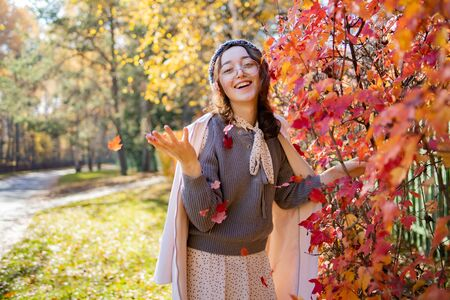 Beautiful woman in glasses throws up red autumn leaves and smiles. Happy woman throws red autumn leaves