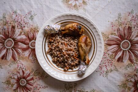 Baked chicken legs with buckwheat. Dish on an old rustic table. View from above Фото со стока