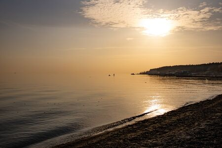Sunset by the sea. The calm water of the sea. Fishermen in the distance at sea