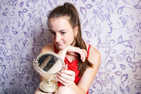 young girl looks in a small vintage mirror on a vintage wall background